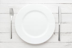 Plate, knife and fork on white background Royalty Free Stock Images