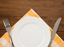 Plate, knife and fork on wood Royalty Free Stock Photos