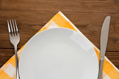 Plate, knife and fork on wood Stock Images