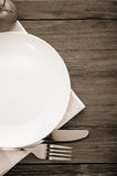 Plate, knife and fork on wood Royalty Free Stock Image