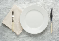 Plate knife and fork on wooden table Royalty Free Stock Photo