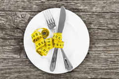 Plate with a knife and fork wrapped in measuring tape on a woode Stock Photo