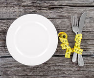 Plate with a knife and fork wrapped in measuring tape on a wooden Royalty Free Stock Image