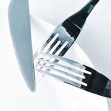 Plate, knife and forks on a set table Stock Photography