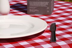 Plate with knife and menu on table Royalty Free Stock Photo