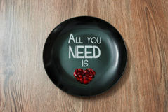 Plate with a lettering and heart symbol. Black plate with the lettering All you need is love and heart shaped pomegranate seeds Royalty Free Stock Photos