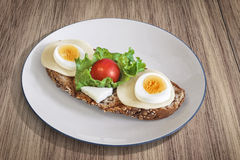 Egg And Cheese Sandwich With Lettuce And Cherry Tomato Served On Porcelain Plate Set On Walnut Wood Surface Royalty Free Stock Photos