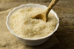 Plate of long grain rice with spoon on wooden background Royalty Free Stock Photography
