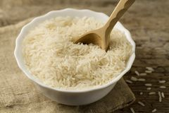 Plate of long grain rice with spoon on wooden background Stock Image