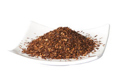 Plate of loose dry Rooibos red tea,  isolated. On the white background Royalty Free Stock Photography