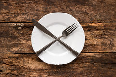 Plate with lying crosswise knife and fork Stock Photography