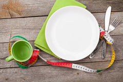Plate with measure tape, cup, knife and fork. Diet food on woode Royalty Free Stock Photo