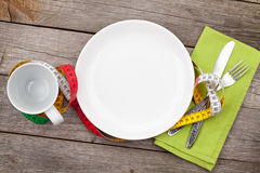 Plate with measure tape, cup, knife and fork. Diet food Royalty Free Stock Images