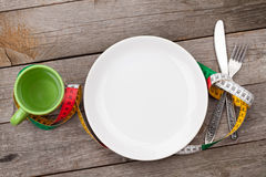 Plate with measure tape, cup, knife and fork. Diet food Stock Images