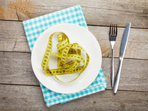 Plate with measure tape, knife and fork. Diet food Royalty Free Stock Photos