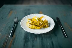 Plate with measuring tape closeup, fat burning. Plate with measuring tape on wooden table closeup. Weight loss diet concept, fat burning Royalty Free Stock Photo