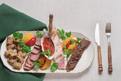 Plate of meat delicacies of wild boar, wild duck, elk, hare top view, close-up Royalty Free Stock Image