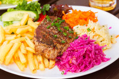 Plate of meat steak with garnish Royalty Free Stock Images
