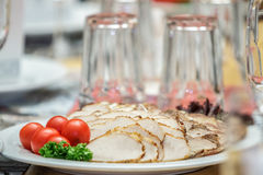 A plate of meats and cherry tomatoes. On the banquet table Royalty Free Stock Images
