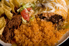 Plate of Mexican food. A very delicious Plate of Mexican food.  On a white plate with a close-up of a smothered  burrito with Mexican rice, refried beans, chips Stock Image