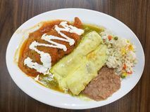 Plate with mexican food, poblano pepper with red sauce, enchiladas with cheese gratin, rice and beans. Plate mexican food poblano pepper red sauce enchiladas royalty free stock photos