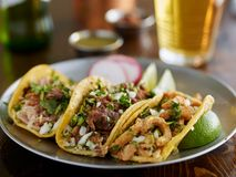 Plate of mexican street tacos garnished with cilantro and onion. Shot with selective focus stock photo
