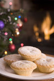 Plate of Mince Pies Log Fire and Christmas Tree. In background Stock Photos