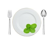 Plate with mint herb, spoon and fork isolated on white Royalty Free Stock Photo