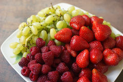 Plate mix of strawberries, raspberries and grapes Royalty Free Stock Images