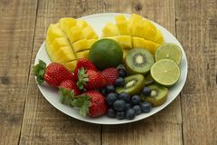 A plate with mixed fruit isolated on white background. Grapes, strawberry, mango, lime, kiwi, lime, citrus, blueberry, berry stock photos