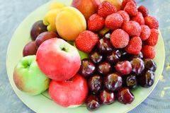 A plate of mixed fruits. A plate of sour cherry, apple, berry, plum and apricot Royalty Free Stock Image