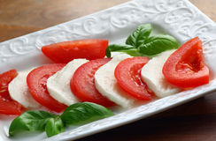 Plate with mozzarella. Close up of sliced mozzarella cheese and fresh red tomatoes Royalty Free Stock Photography