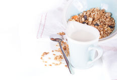 Plate of muesli and milk jug on a white background Royalty Free Stock Photos