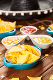 Plate of nachos with different dips Stock Photo