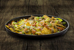 Plate of nachos. Isolated on a wooden table royalty free stock photo