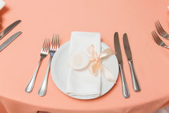 Plate with napkin with pink ribbon on the table in restaurant Stock Images