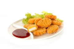Plate of nuggets with dip sauce, one nugget cut Stock Photo