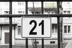The plate with number 21 is hanging on the parking lot. royalty free stock photography