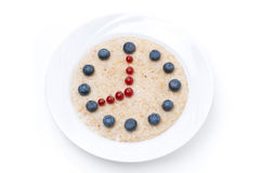 Plate of oatmeal with berries in the form of dial, isolated. On white Royalty Free Stock Photo
