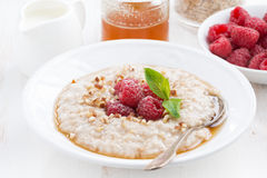 Plate of oatmeal with fresh raspberries and honey, close-up. Horizontal Stock Photos