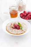 Plate of oatmeal with fresh raspberries and honey, vertical Royalty Free Stock Image