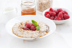 Plate of oatmeal with fresh raspberries and honey on white table Royalty Free Stock Photos