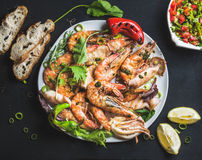 Free Plate Of Roasted Tiger Prawns And Octopus Pieces With Fresh Leek, Salad, Peppers, Lemon, Bread, Pesto Sauce Over Black Royalty Free Stock Photo - 74909815