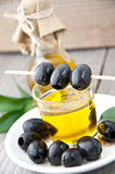 Plate with olives and a bottle of olive oil. On a wooden background Stock Images