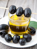 Plate with olives and a bottle of olive oil. On a wooden background Royalty Free Stock Photos