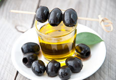 Plate with olives and a bottle of olive oil. On a wooden background Stock Photos