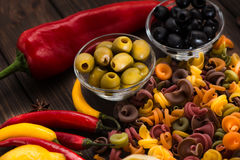 Plate with olives, pasta, sweet and bitter peppers. Ingredients for Italian dishes. Close-up Stock Photo