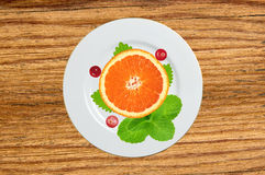 Plate with orange slice, mint herb and berry on wooden table Stock Photography
