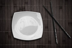 Plate over bamboo placemat with chopsticks Royalty Free Stock Photo