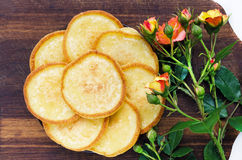 Plate with pancakes on a brown wooden board with rose flowers Royalty Free Stock Image